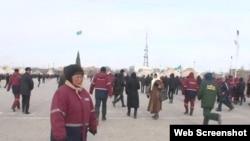 """Люди в рабочих спецовках на площади в Жанаозене. 16 декабря 2011 года. Скриншот с видеопортала """"Стан.кз""""."""