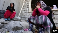 Iraqi Yazidi women who fled the violence in the northern Iraqi town of Sinjar sit outside a school, where they are taking shelter in the Kurdish city of Dohuk in Iraq's autonomous Kurdistan region, on August 5.