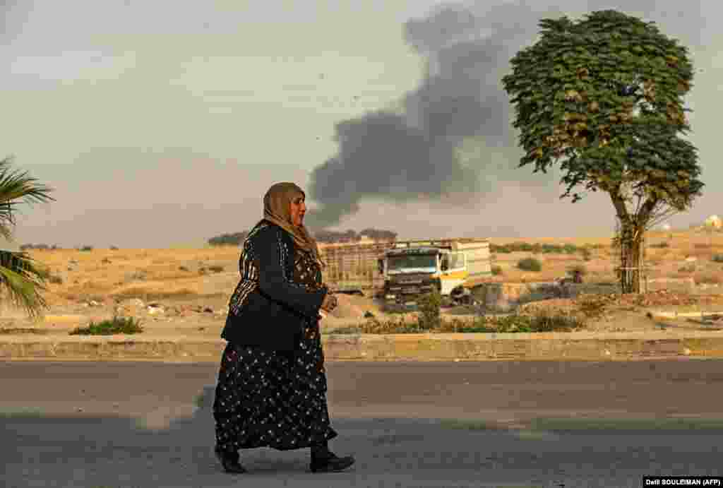 A Syrian woman walks past a smoke cloud in the distance following a Turkish bombardment of the northeastern Syrian border town of Ras al-Ain in Hasakeh Province. (Delil Souleiman/AFP)