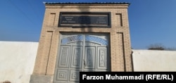 Gerbang tinggi yang mengarah ke pemakaman Yahudi di Khujand menampilkan tanda dalam bahasa Tajik, Ibrani, dan Inggris.