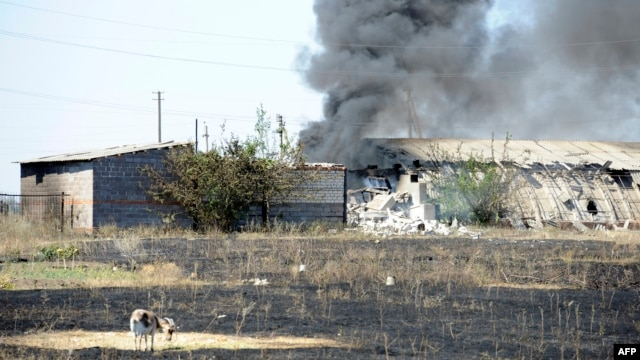 Smoke billows over a damaged building after shelling on the outskirts of the small Ukrainian border town of Novoazovsk, which Kyiv said on August 28 had been seized by Russian tanks and troops.