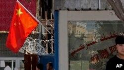 Китайский флаг на одной из улиц Пейзавата в китайской провинции Синьцзян.