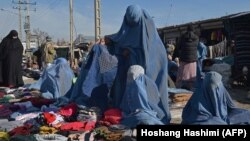 Burqa-clad women sell clothes along a road in Afghanistan (file photo)