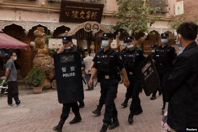 Қашқар көшесін күзетіп жүрген полиция қызметкерлері. Қытайдың Шыңжаң аймағы, 4 мамыр 2021 жыл.