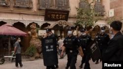 Qashg'ar shahri ko'chasidan Xitoy politsiyasi xodimlari o'tib bormoqda. 2021 - yil, bahor.