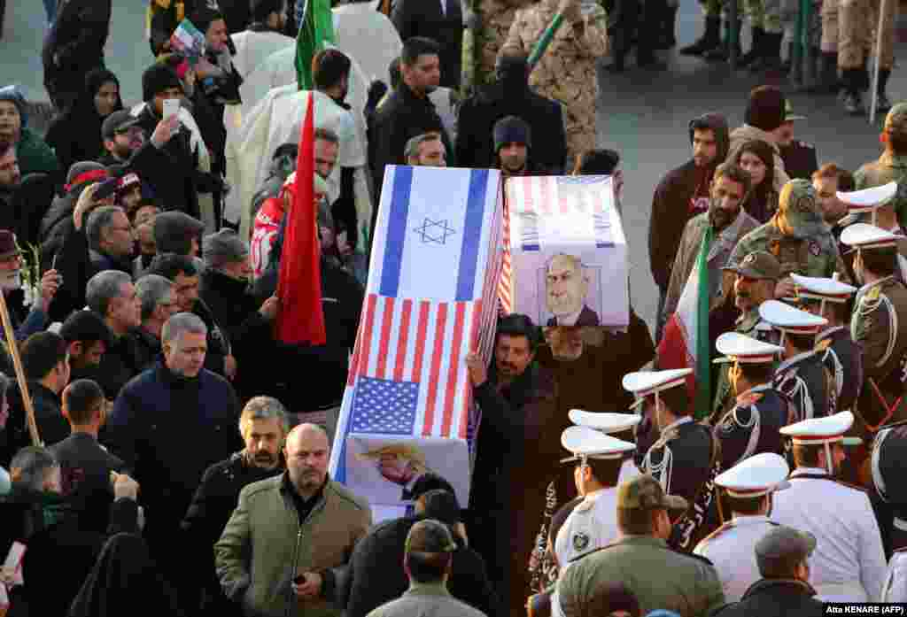 Mourners carry mock coffins with images of U.S. President Donald Trump and Israeli Prime Minister Benjamin Netanyahu.