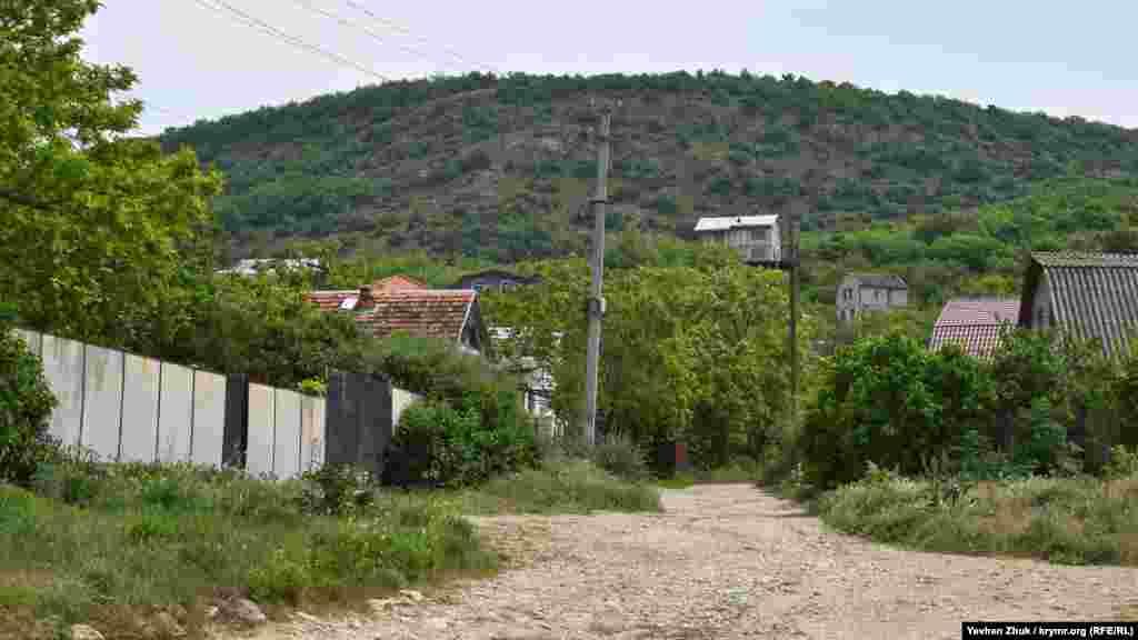 Домики как бы взбираются на склон горы Каю