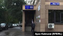 Қазақстандықтарды шетелге жіберумен айналысатын компания орналасқан ғимаратқа кіріп бара жатқан адам. Алматы, 1 қазан 2019 жыл.