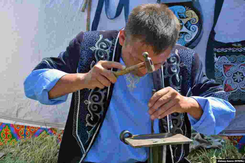 А у этого мужчины мирное занятие – он дает мастер-класс по изготовлению металлических браслетов. Мастер-классы были и по другим традиционным ремеслам – по работе с деревом, с костью, на гончарном круге и другие.