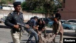 Policët e ndihmojnë një të plagosuri pas një sulmi të mëparshëm me bombë në Pakistan