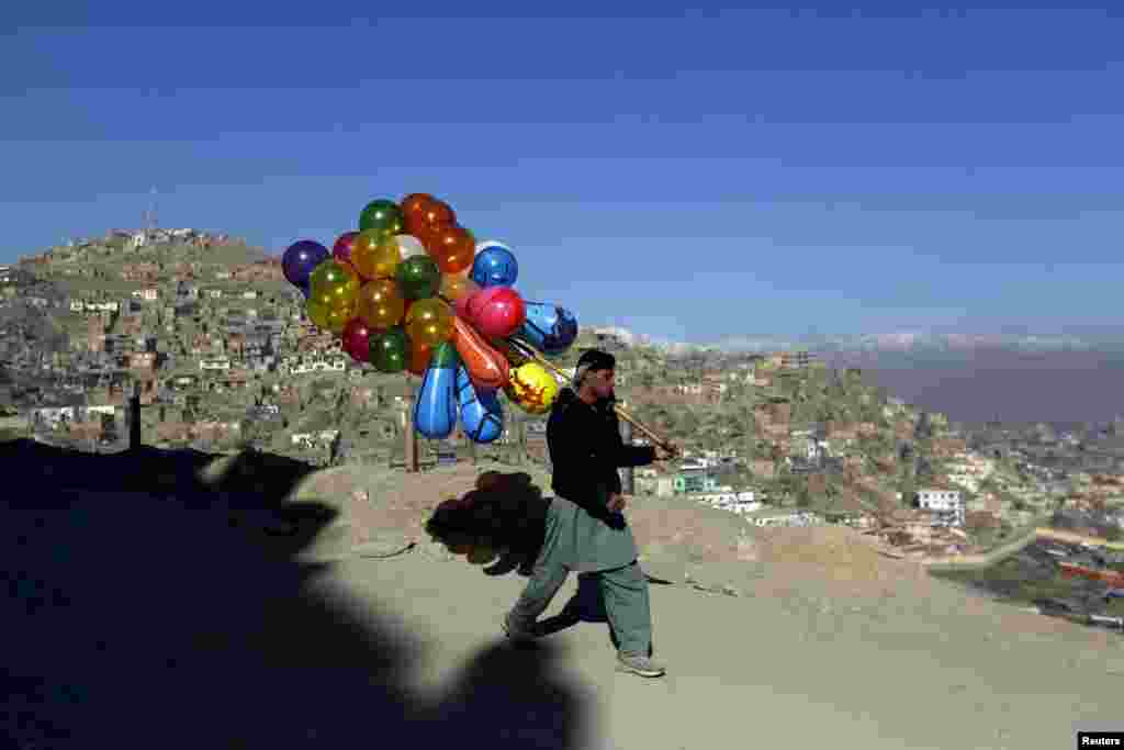 An Afghan man holds balloons for sale in Kabul. (Reuters/Mohammad Ismail)
