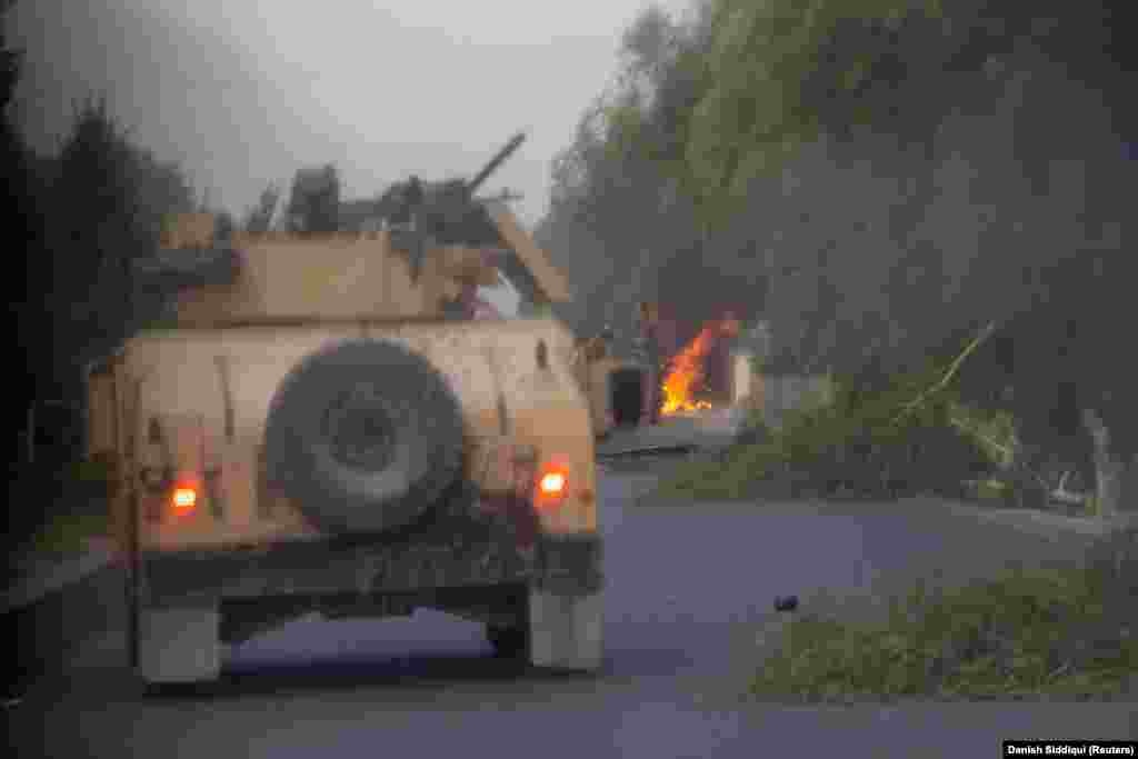A Humvee hit by a rocket-propelled grenade (RPG) burns during an early morning mission by Afghan special forces on July 13. The elite troops were attempting to rescue police commander Ahmad Shah, who was besieged by Taliban militants on the outskirts of the southern city of Kandahar.