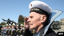 Ukrainian World War II veterans stand at attention during Ukraine's national anthem. Some consider the song's warlike theme to be outdated.
