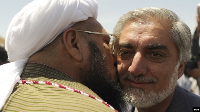 Passions have been inflamed in Afghanistan after a running mate of presidential candidate Abdullah Abdullah (right) was photographed commemorating the death of former Iranian Supreme Leader Ayatollah Khomeini. (file photo)