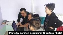 Дархан Бегайдаров балаларға компьютерде видео монтаждауды үйретіп отыр. Суретшінің жеке архивіндегі фото.