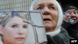 Сторонница бывшего премьер-министра Украины Юлии Тимошенко держит ее портрет. Киев, 27 ноября 2011 года.