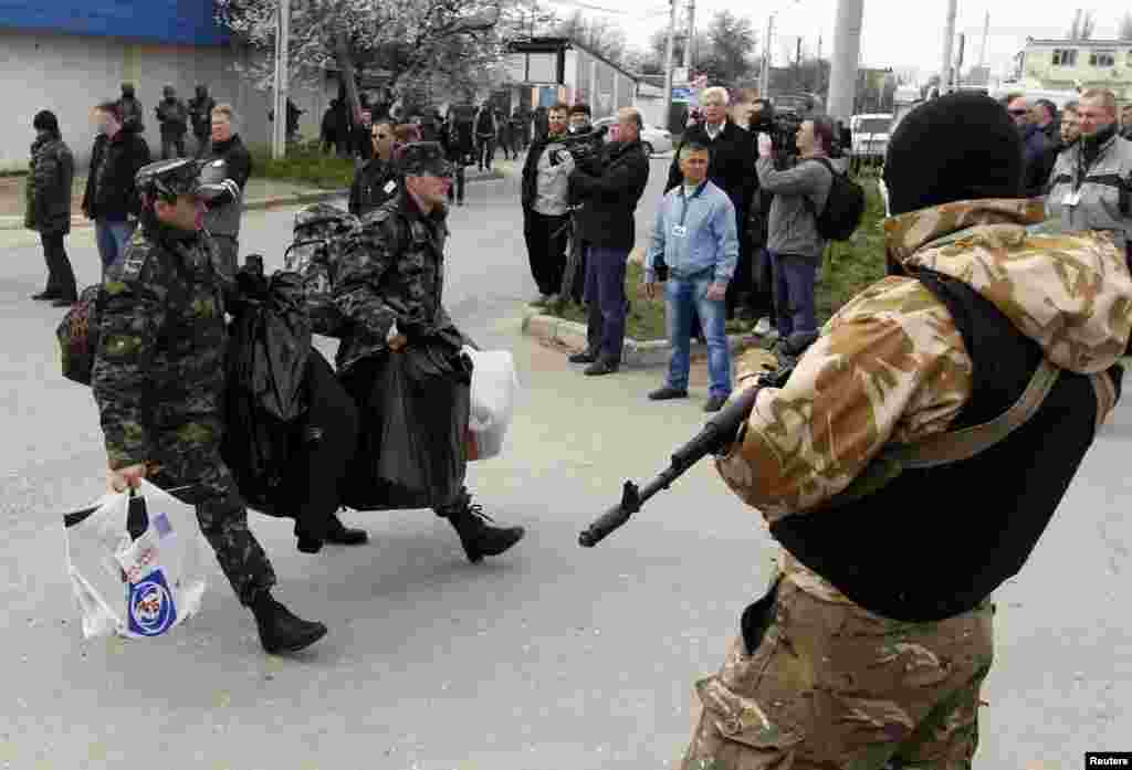 Ukraine -- Ukrainian servicemen carry their belongings as they pass by an armed man while leaving the territory of the naval headquarters in Sevastopol, March 19, 2014