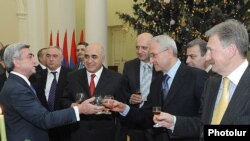 President Serzh Sarkisian, left, assures businessmen that the economy will improve in the new year, but some reports disagree with the president's optimism.