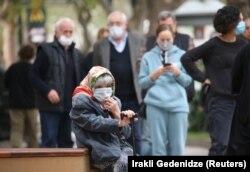 Коронавирус пандемиясы кезінде өтіп жатқан сайлау күні учаске сыртында күтіп отырған егде жастағы әйел. Тбилиси, Грузия, 31 қазан 2020 жыл.