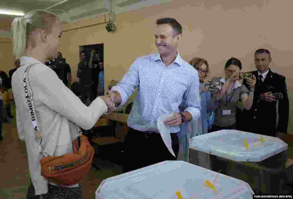 Russian opposition politician Aleksei Navalny shakes hands with his daughter Daria as he votes at a polling station during the Moscow city council elections on September 8.The elections have drawn fierce protests after several opposition candidates allied with Navalny were barred from standing.