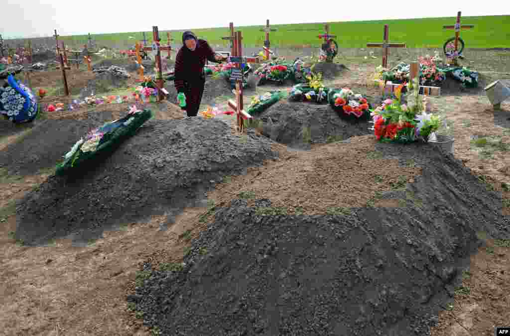 A woman tends a grave at a cemetery in Ceadir-Lunga.