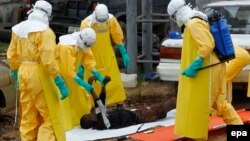 Либерия дәрігерлері Эбола вирусынан көз жұмған адамның денесін әкетіп барады. 9 қыркүйек 2014 жыл.