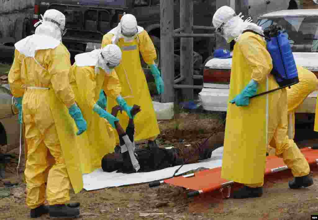 Табиблар Эболадан үдгән дип саналган кешене алып китә. Моровия, Либерия. 9 сентябрь 2014