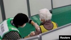 Një qytetare japoneze duke u vaksinuar në Tokio.