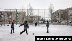 Қаладағы шағын стадионда футбол ойнап жүрген балалар. Ақсу. 22 наурыз 2018 жыл.