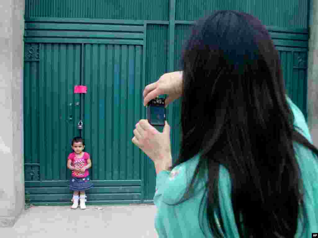 A Pakistani woman photographs her daughter at a gate of the compound in Abbottabad, Pakistan, where bin Laden was killed. Photo by Aqeel Ahmed for AP.