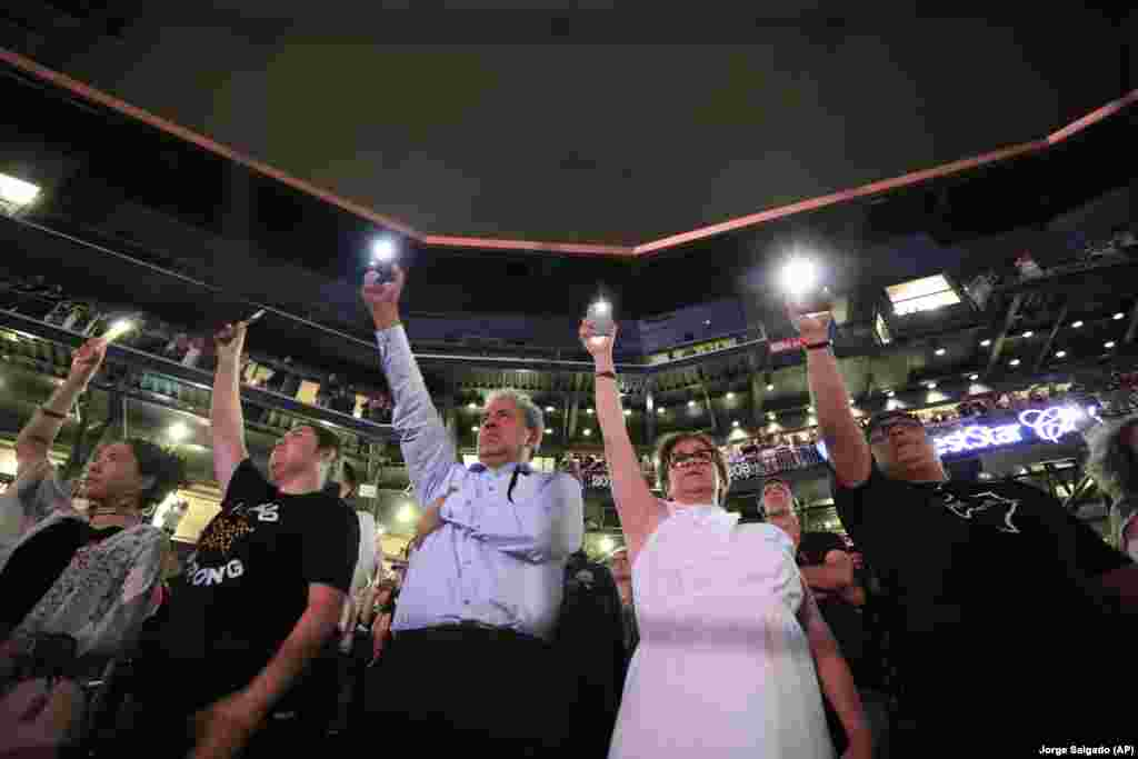 People hold up their cellphones as the names of the victims of a mass shooting are read during a memorial service on August 14, 2019, at Southwest University Park, in El Paso, Texas. (AP Photo/Jorge Salgado)