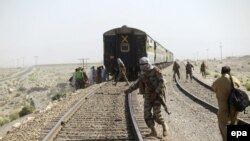 Pakistani soldiers stand at the scene of bomb blast that targeted the rail track near the town of Mach, southeast of Quetta, capital of the southwestern Balochistan Province.
