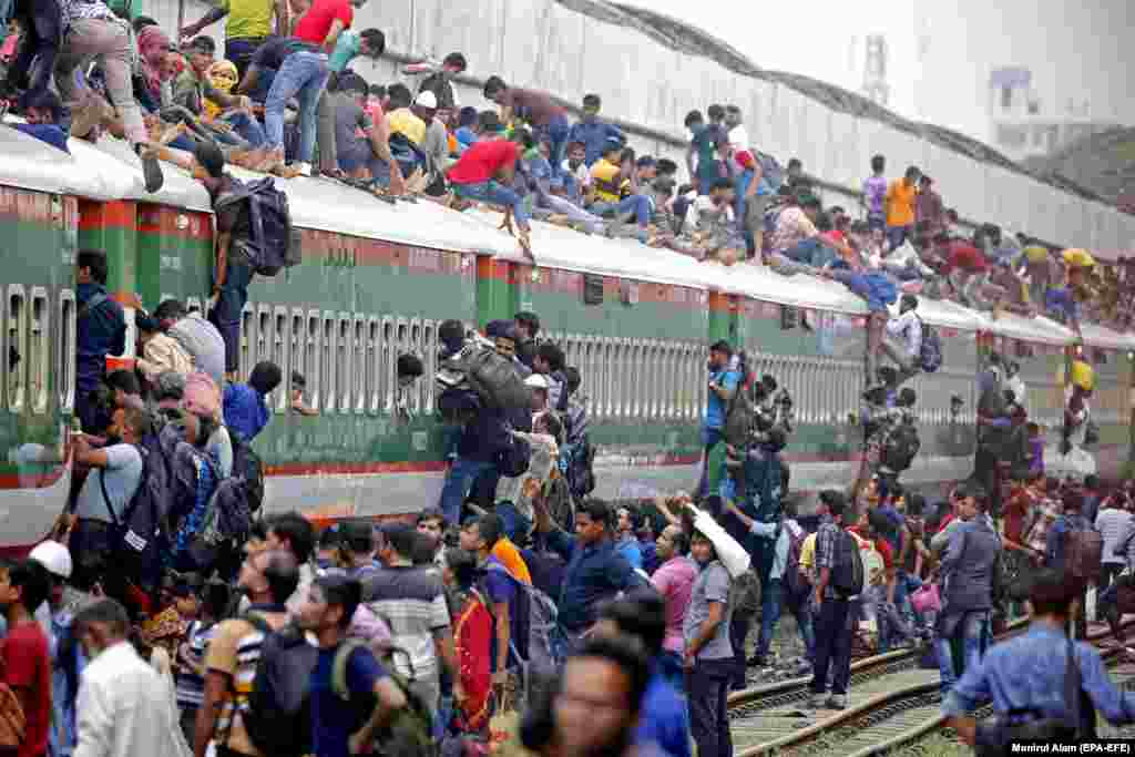 People climb on the roof of an overcrowded train as they travel to their home villages to celebrate Eid al-Adha at the Kamlapur Railway Station in Dhaka, Bangladesh. Eid al-Adha is the holiest of the two Muslims holidays celebrated each year. It marks the yearly Muslim pilgrimage to visit Mecca. (epa-EFE/Monirul Alam)