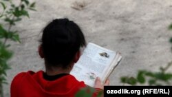 Uzbekistan - school girl is reading biology book at home, 15May2012