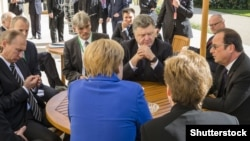 German Chancellor Angela Merkel (center, facing away), Russian President Vladimir Putin (left to right), Ukrainian President Petro Poroshenko, and French President Francois Hollande met in Berlin on the crises in Ukraine and Syria.