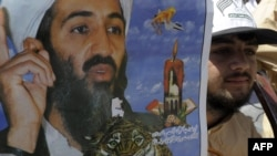 A Pakistani Islamist holds a poster of Osama bin Laden during a protest on the outskirts of Quetta
