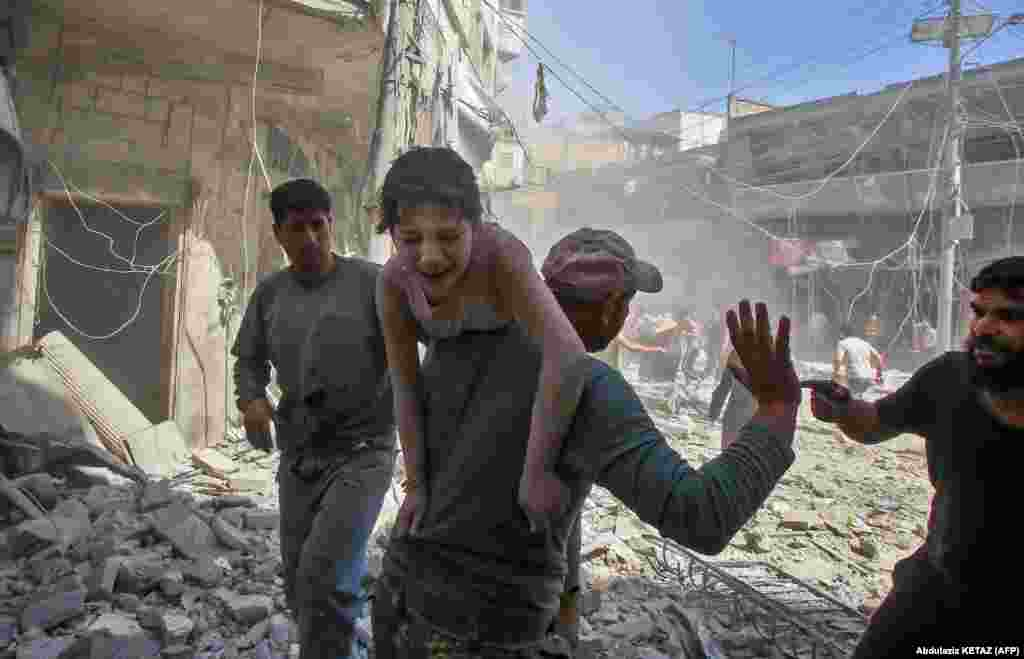 A man evacuates an injured child after a reported air strike by Syrian forces and their allies on the Syrian town of Maaret Al-Noman in the southern Idlib province on May 26. (AFP/Abdulaziz Ketaz)