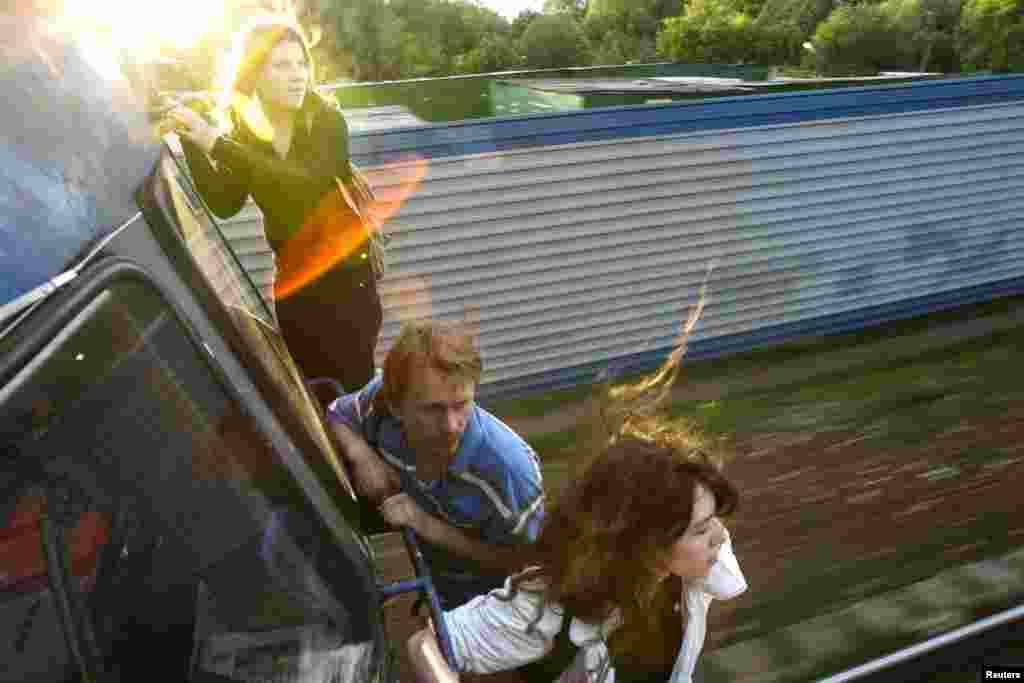 Activists Yekaterina Samutsevich (left), Oleg Vorotnikov (center), and Natalia Sokol travel on the outside of a commuter train near Moscow after refusing to buy tickets in June 2008. Samutsevich later became a member of Pussy Riot.
