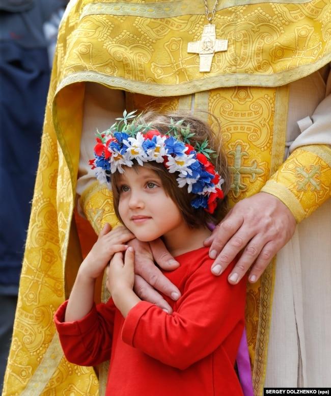 Дівчинка зі священиком УПЦ Київського патріархату під час відзначення Хрещення України-Руси. Київ, 28 липня 2017 року