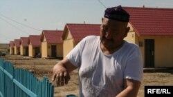 Айтбай Кесперов закрывает калитку во дворе дома в новом микрорайоне Саялы. Алматы,11 июля 2009 года.