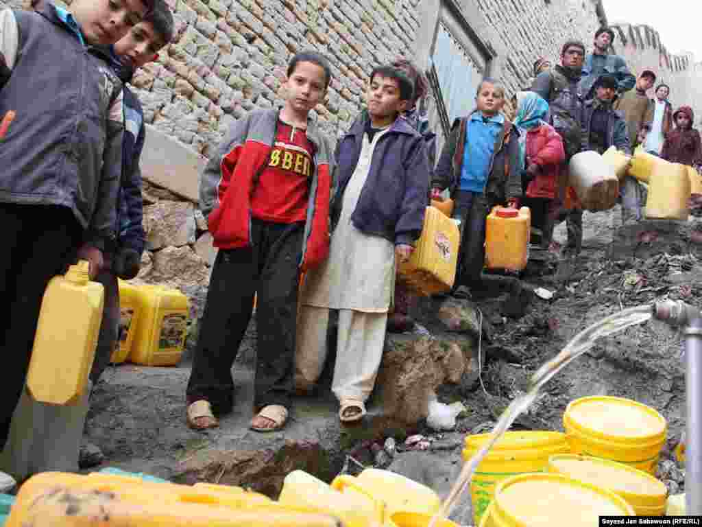 Afghan children wait to fill cans from a community tap in Kabul.
