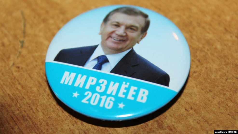 A campaign button for acting President Shavkat Mirziyaev