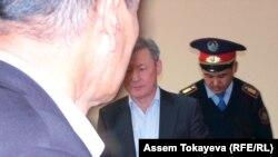 Жаксыбек Кулекеев (в центре) входит в зал суда.