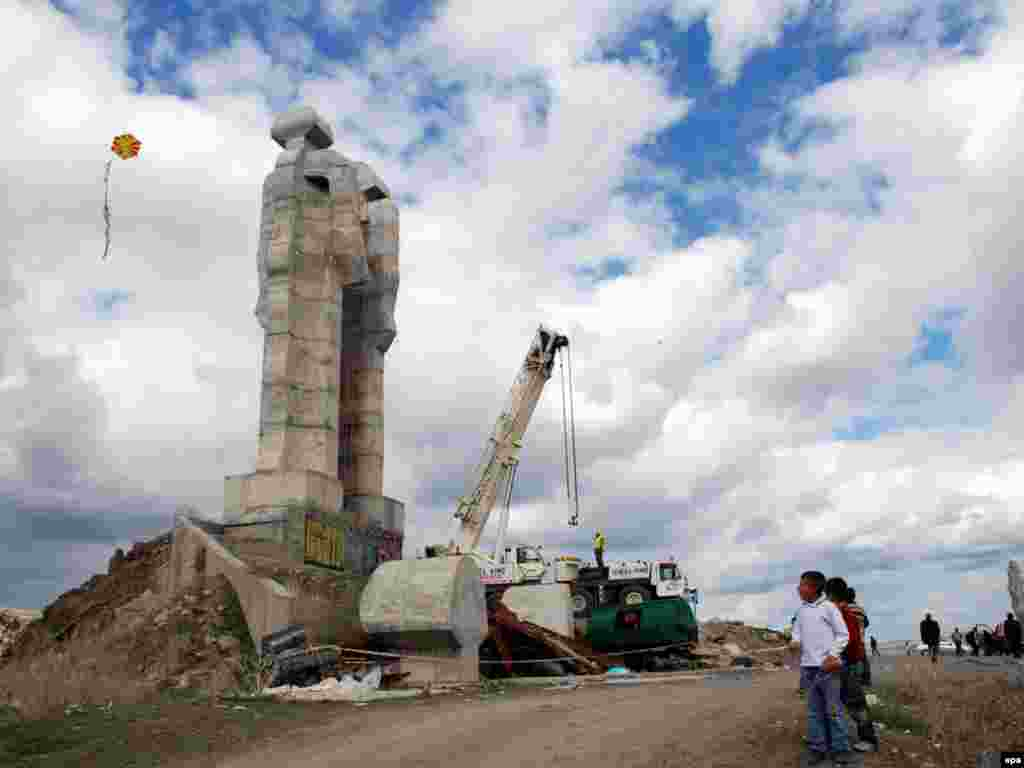"Turkish children play in front of the unfinished statue of ""Peace and Brotherhood"" in Kars, near the border with Armenia. Local officials decided in February to demolish the monument. Photo by EPA."