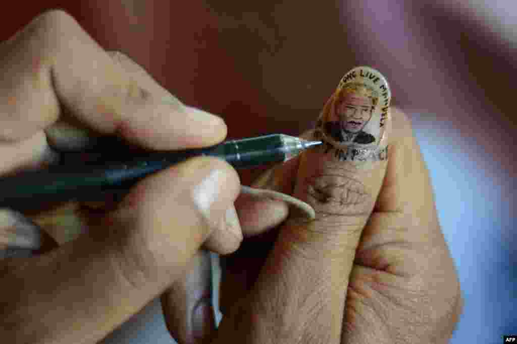 An Indian artist draws a miniature portrait of former South African President Nelson Mandela on his thumbnail as part of his homage in Siliguri. (AFP/Diptendu Dutta)