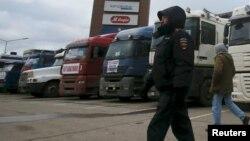 Жүк көліктерінің алдында жүрген Ресей полициясы қызметкері. (Көрнекі сурет)