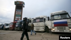A police officer walks past a line of trucks whose drivers are taking part in a protest against a new fee at a parking lot in the Moscow region in December 2015.