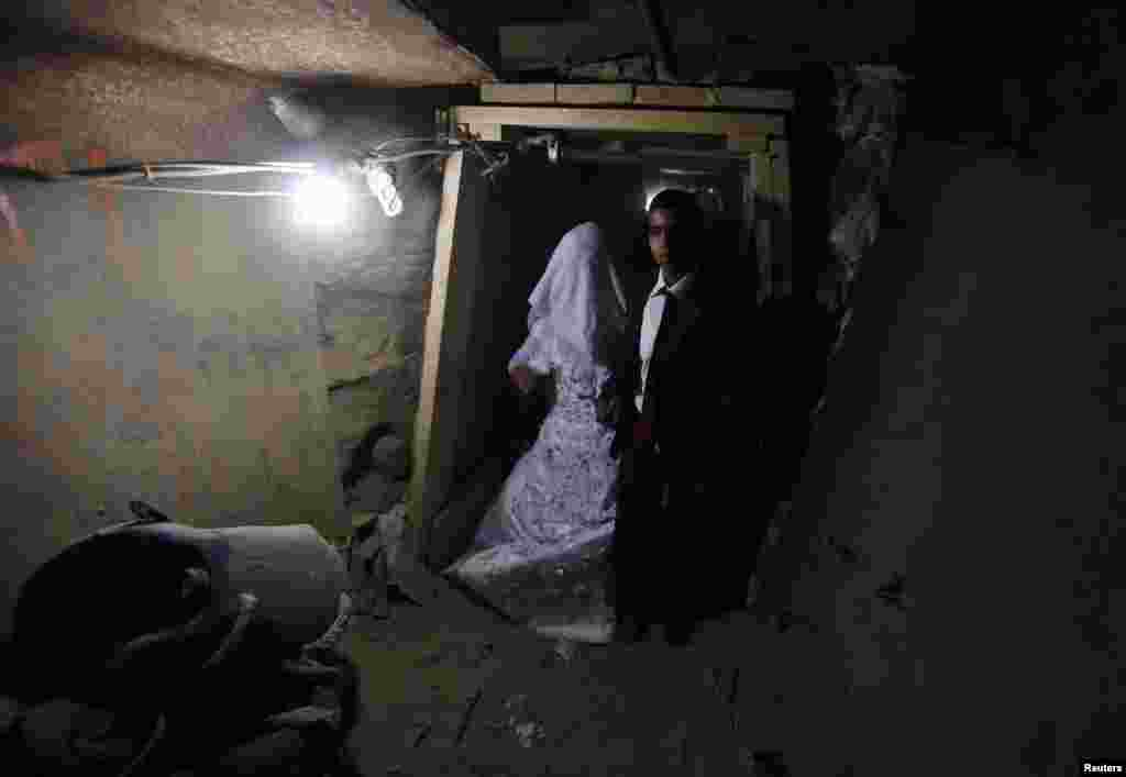 Palestinian groom Emad al-Malalha, 21, walks with Manal Abu Shanar, 17, his Egyptian bride inside a smuggling tunnel beneath the Gaza-Egypt border in the southern Gaza Strip. (Reuters/Ibraheem Abu Mustafa)
