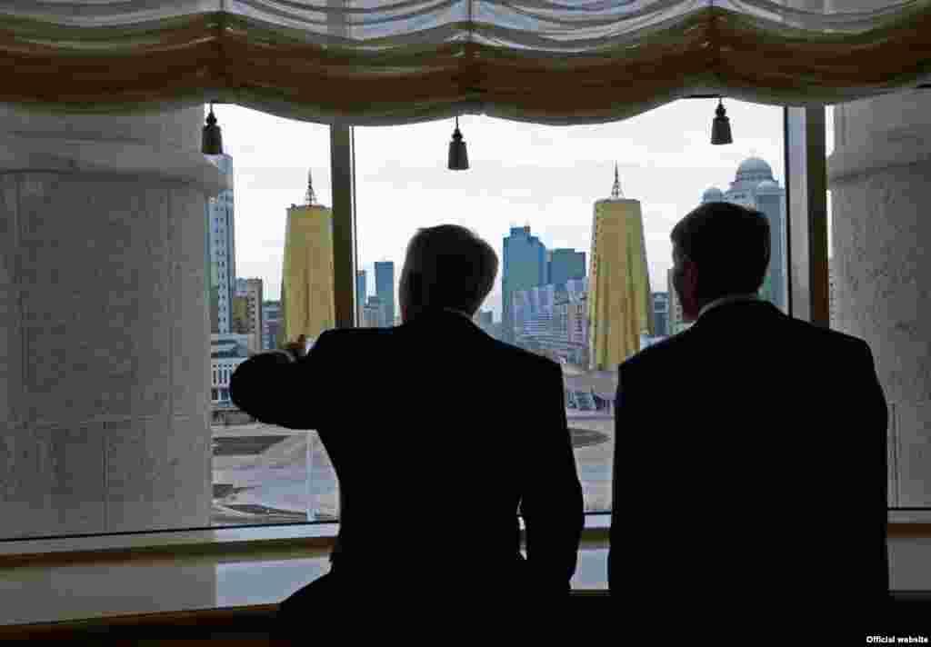 Нурсултан Назарбаев показывает Алмазбеку Атамбаеву открывающийся из окна своей резиденции в Астане вид. 7 ноября 2014 года.