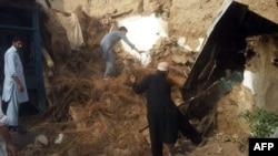 Люди у разрушенного землетрясением дома. Пакистан, 26 октября 2015 года.